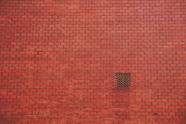 Muro di mattoni rossi con uno sfiato quadrato