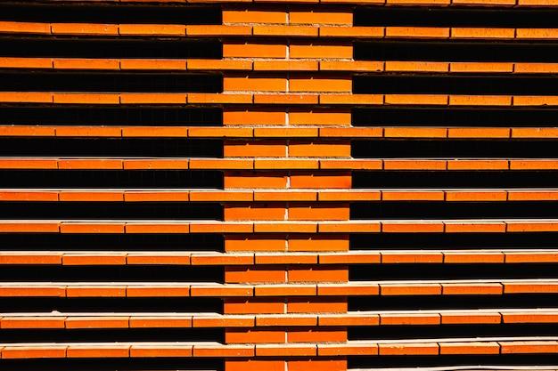 Muro di mattoni rossi intenso al sole.