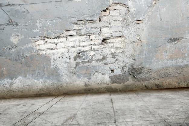 Muro di mattoni rovinato con pavimento sporco