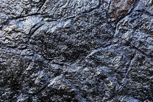 Muro di mattoni scuro, trama di blocchi di pietra nera, panorama ad alta risoluzione