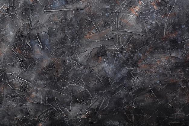 Muro di pietra con texture grigio scuro. schermo intero come