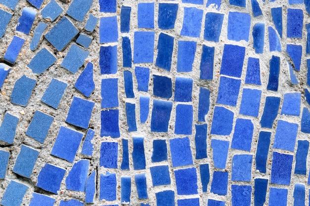 Muro di tessere di mosaico schiacciate blu come sfondo.