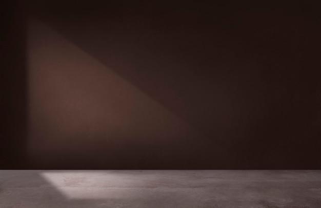 Muro marrone scuro in una stanza vuota con pavimento in cemento