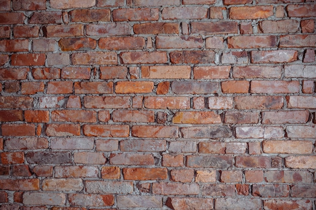 Muro realizzato con mattoni marroni mescolati a caso con piccoli neri.