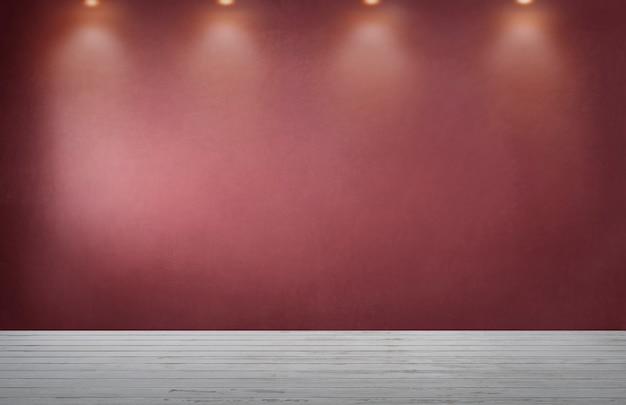 Muro rosso con una fila di faretti in una stanza vuota
