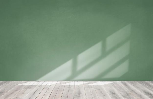 Muro verde in una stanza vuota con un pavimento in legno