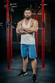 Muscolare uomo forte con tatuaggi e barba in posa in canottiera bianca e pantaloncini blu in palestra.