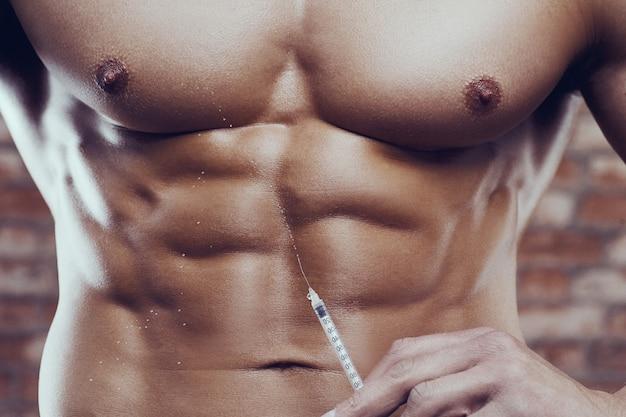 Muscoli dell'iniezione della siringa steroide dell'uomo forte del culturista