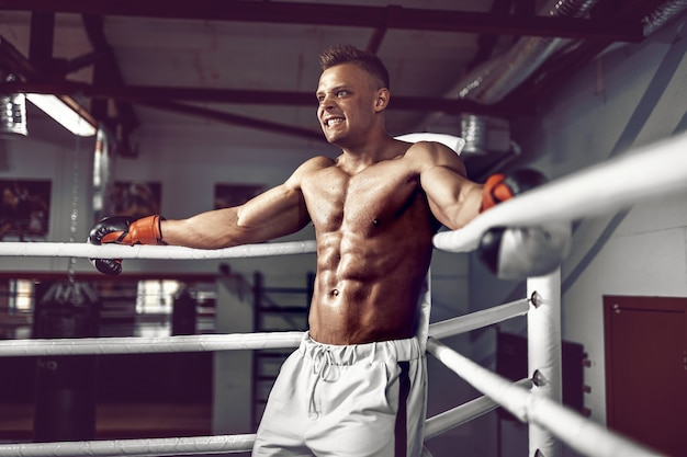 Muscoloso kick boxer professionista appoggiato alle corde nell'angolo del ring durante l'allenamento per la partita successiva