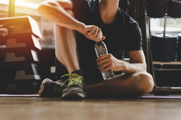 Muscoloso uomo caucasico prendendo pausa relax acqua potabile mentre si riposa dopo l'allenamento in palestra