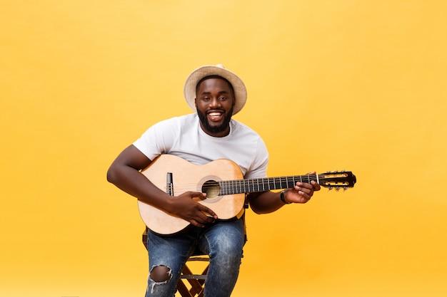 Muscoloso uomo nero che suona la chitarra, indossa jeans e canottiera bianca. isolare su sfondo giallo.