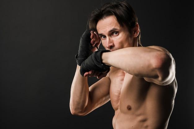 Muscoloso uomo senza camicia con guantoni da boxe