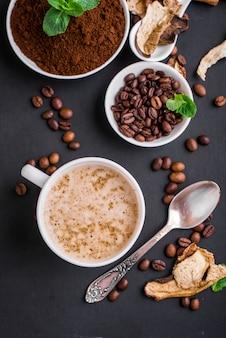 Mushroom chaga coffee superfood funghi e chicchi di caffè freschi e asciutti sulla superficie scura con la menta.