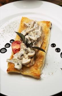Mushtoom saltato, pollo alla stroganoff su un pezzo di pane. antipasta in un piatto bianco decorato con posate sul tavolo di legno