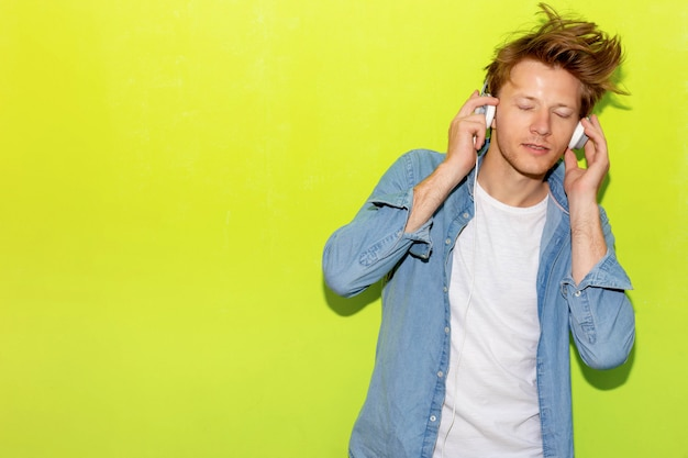 Musica d'ascolto attraente giovane ragazzo bello utilizzando la cuffia.