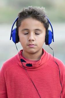 Musica d'ascolto del bambino con le cuffie e gli occhi chiusi