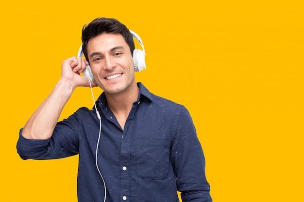 Musica d'ascolto del giovane con le cuffie nell'applicazione di canzone della playlist isolata sulla parete gialla