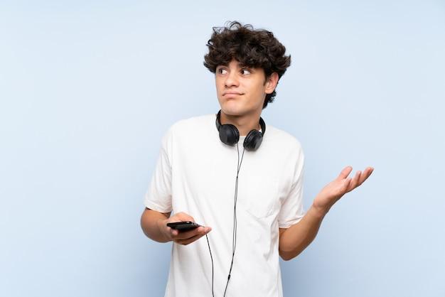 Musica d'ascolto del giovane con un cellulare sopra la parete blu isolata che fa gesto di dubbi mentre sollevando le spalle