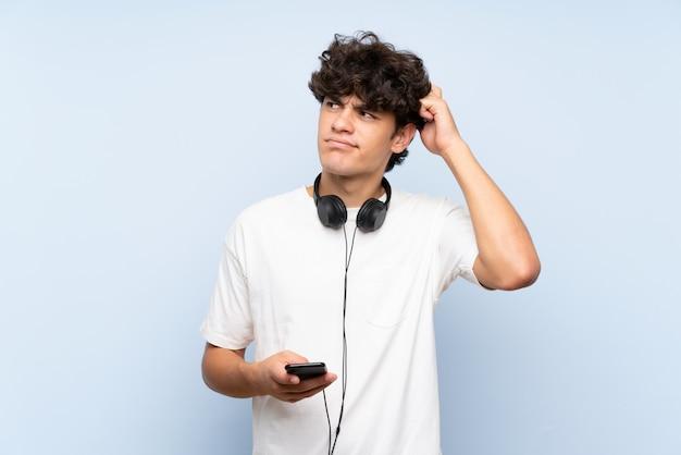 Musica d'ascolto del giovane con un cellulare sopra la parete blu isolata che ha dubbi e con l'espressione confusa del fronte
