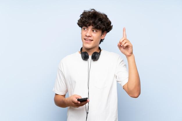 Musica d'ascolto del giovane con un cellulare sopra la parete blu isolata che intende realizzare la soluzione mentre sollevando un dito su