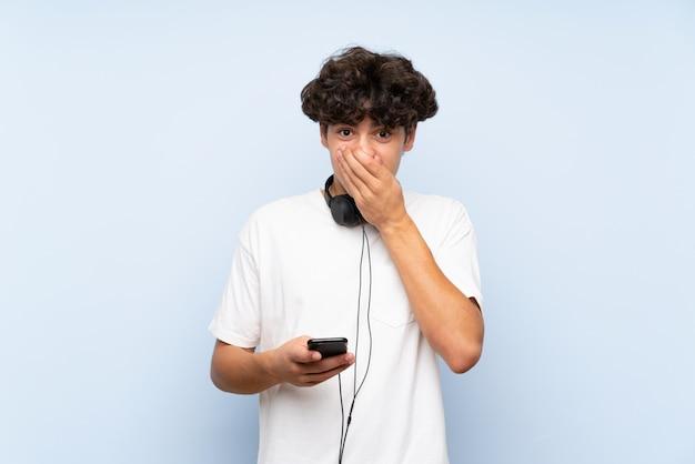 Musica d'ascolto del giovane con un cellulare sopra la parete blu isolata con espressione facciale di sorpresa