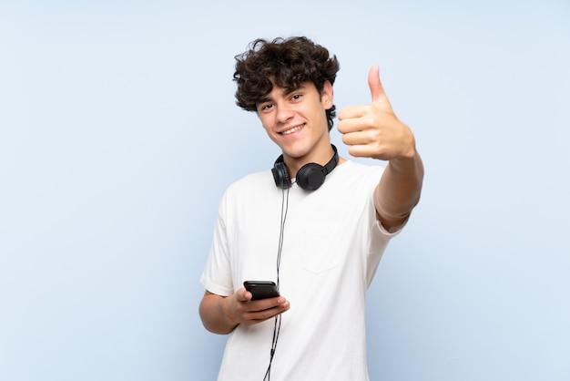 Musica d'ascolto del giovane con un cellulare sopra la parete blu isolata con i pollici su perché è successo qualcosa di buono