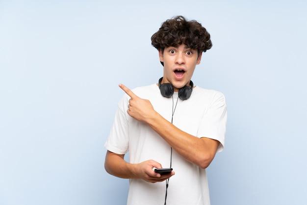 Musica d'ascolto del giovane con un cellulare sopra la parete blu isolata sorpresa e lato indicante