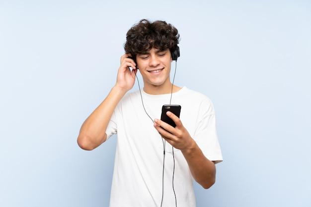 Musica d'ascolto del giovane con un cellulare sopra la parete blu isolata