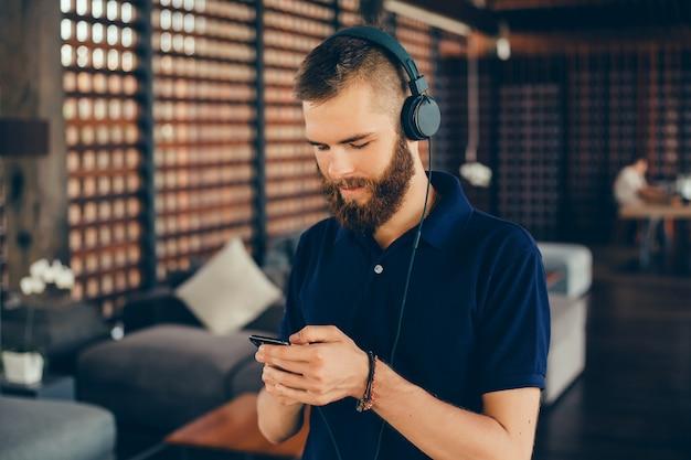 Musica d'ascolto del giovane in cuffie, facendo uso dello smartphone, ritratto all'aperto dei pantaloni a vita bassa