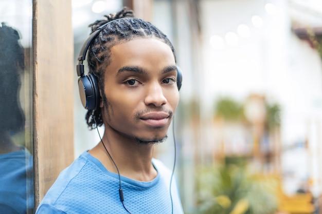 Musica d'ascolto del giovane ragazzo freddo con le cuffie
