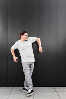 Musica d'ascolto del giovane sulla cuffia tramite il telefono cellulare che sta contro la parete nera