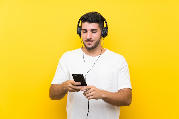 Musica d'ascolto del giovane uomo bello con un cellulare sulla parete gialla