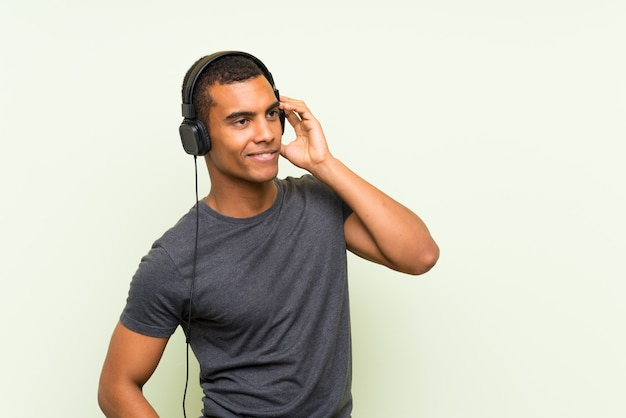 Musica d'ascolto del giovane uomo bello con un cellulare