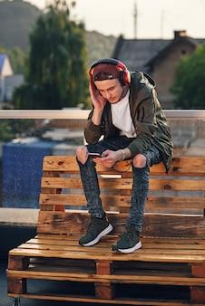 Musica d'ascolto del giovane uomo bello in cuffie e telefono usando sul tetto di fabbricato industriale al tramonto.