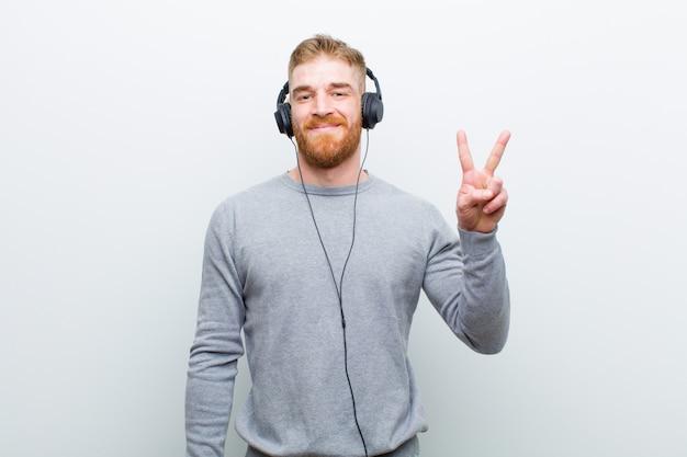 Musica d'ascolto del giovane uomo capo rosso con le cuffie contro bianco