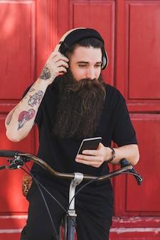 Musica d'ascolto del giovane uomo elegante del ciclista sulle cuffie contro la porta di legno
