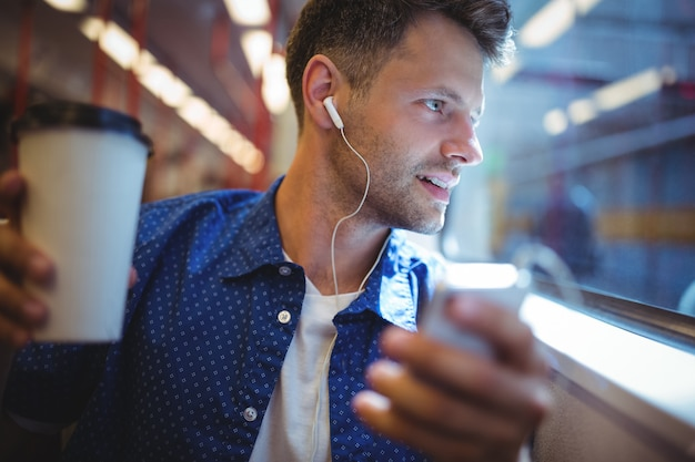 Musica d'ascolto dell'uomo bello sul telefono cellulare mentre mangiando caffè