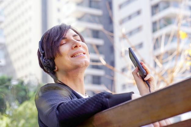 Musica d'ascolto dell'uomo con il suo smartphone