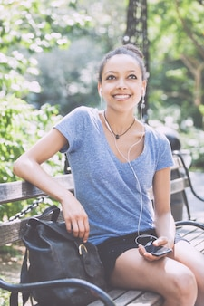 Musica d'ascolto della bella giovane donna della corsa mista con le cuffie al parco