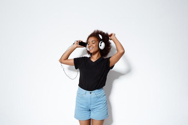 Musica d'ascolto della bella ragazza africana in cuffie sopra la parete bianca.