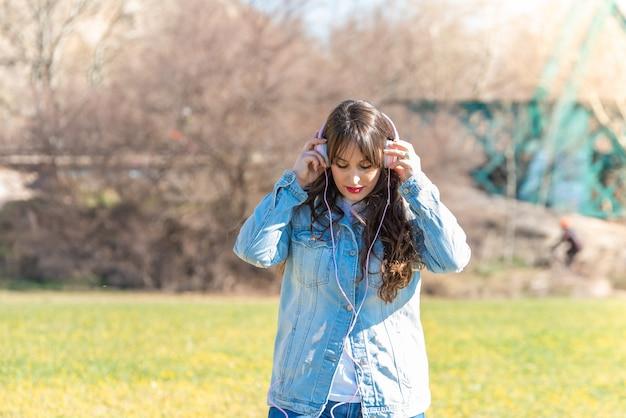 Musica d'ascolto della bella ragazza all'aperto