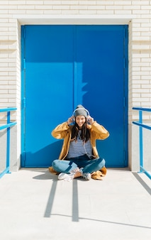 Musica d'ascolto della donna felice sullo smart phone che si siede contro la porta blu all'aperto