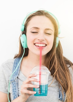 Musica d'ascolto della donna sul succo bevente della cuffia con paglia contro fondo bianco
