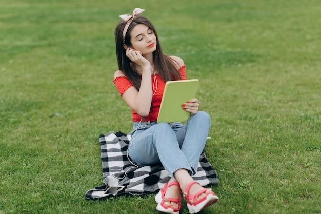 Musica d'ascolto della donna tramite la cuffia avricolare e il libro di lettura in parco