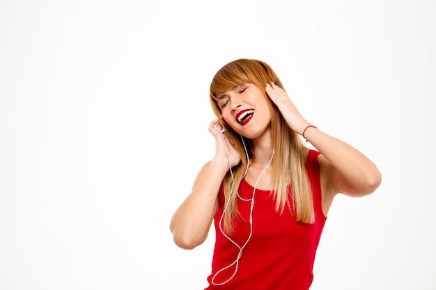 Musica d'ascolto della giovane bella donna in cuffie sopra la parete bianca