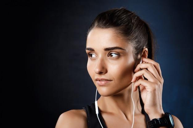 Musica d'ascolto della giovane bella ragazza allegra sopra la parete scura.