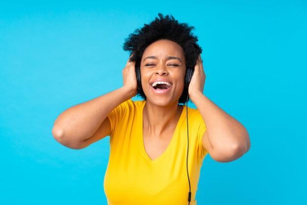 Musica d'ascolto della giovane donna afroamericana con un cellulare