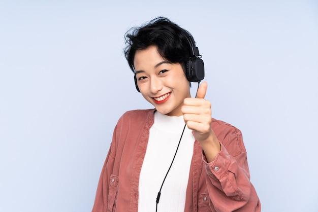 Musica d'ascolto della giovane donna asiatica e con il pollice in su