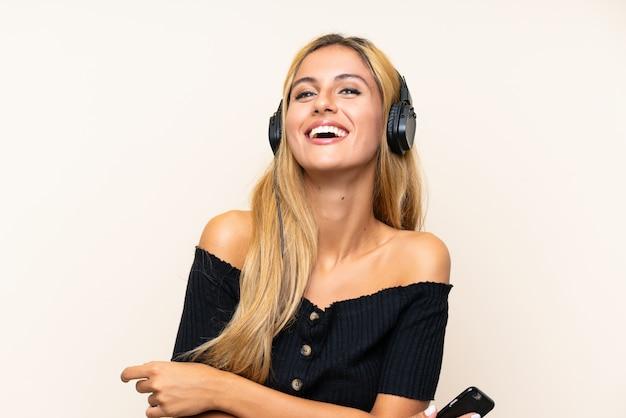 Musica d'ascolto della giovane donna bionda con un cellulare
