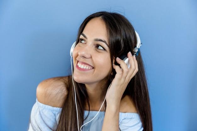 Musica d'ascolto della giovane donna con i trasduttori auricolari